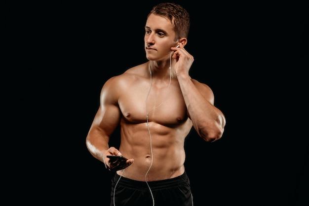 黒に分離されたスマートフォンでイヤホンで音楽を聴く筋肉胴とセクシーなボディービルダー