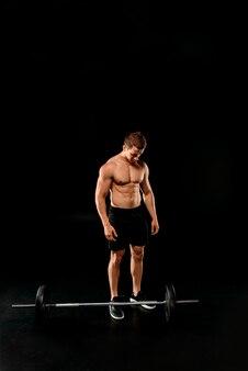 黒に分離されたバーベルの近くに筋肉の胴体立ってセクシーなボディービルダー