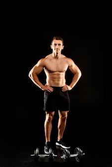 黒に分離されたダンベルの近くのお尻に手で立っている筋肉の胴体を持つセクシーなボディービルダー