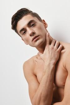 Сексуальный брюнет парень обнаженный торс рукой возле лица.