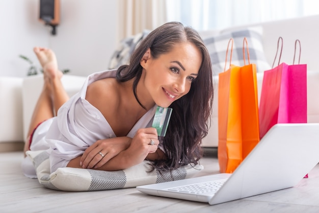 Sexy brunette female shopping online while lying on the floor in light living room, with a pillow under her elbows, a debit card in her hand, smiling. orange and pink paper shopping bags next to her.