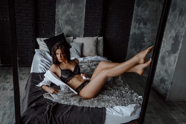 Сексуальная брюнетка девушка в черном белье, лежа на кровати