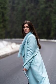 Sexy brunette girl poasing on road on winter mountains table. glamorous young woman wearing stylish blue long coat. fashion, business and beautiful people concept..
