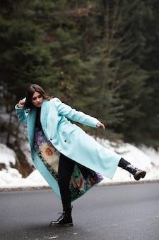 Сексуальная брюнетка девушка позирует и повеселиться на дороге в горах зимой