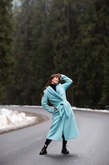 Сексуальная брюнетка девушка позирует на дороге в горах зимой