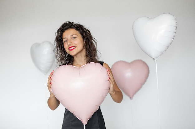 Сексуальная брюнетка девушка позирует с воздушными шарами в форме сердца на белом фоне.