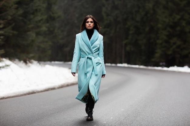 Сексуальная брюнетка девушка гуляет по дороге в горах зимой