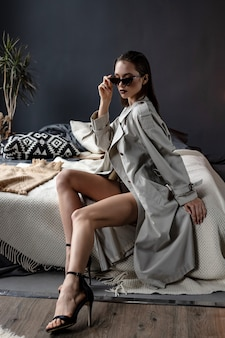 침대에 트렌치 코트와 란제리를 입고 섹시한 갈색 머리 소녀