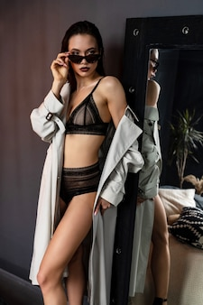 Sexy brunette girl wearing trench coat and lingerie