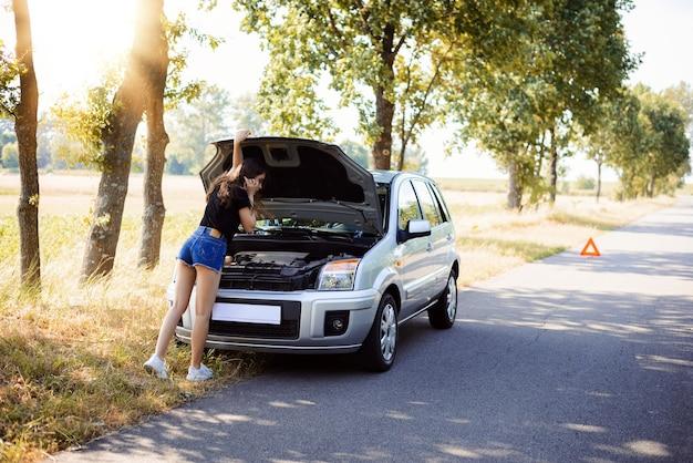 Сексуальная брюнетка девушка с длинными голыми ногами стоит возле разбитой машины