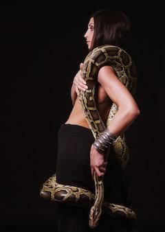 Sexy brunette holding python