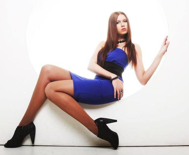 円に座っている青いドレスのセクシーなブルネット