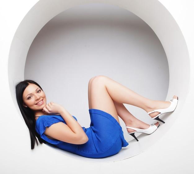 Сексуальная брюнетка в синем платье сидит в кругу