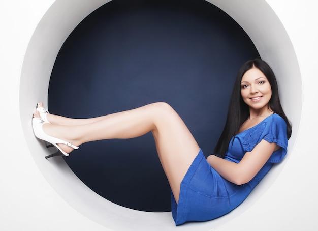 동그라미에 앉아 파란 드레스에 섹시 한 갈색 머리