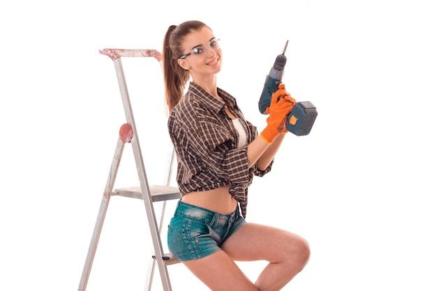 セクシーなブルネットの女性は、スタジオで白い背景に分離された手とはしごのドリルでアパートを改装します