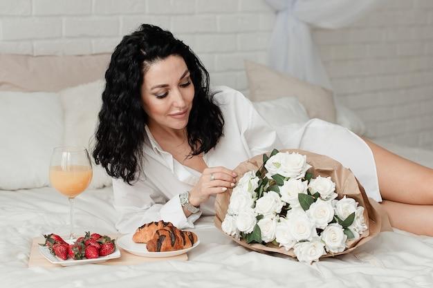 흰 셔츠에 섹시한 갈색 머리 모델은 음식과 꽃의 꽃다발과 함께 침대에 놓여 있습니다