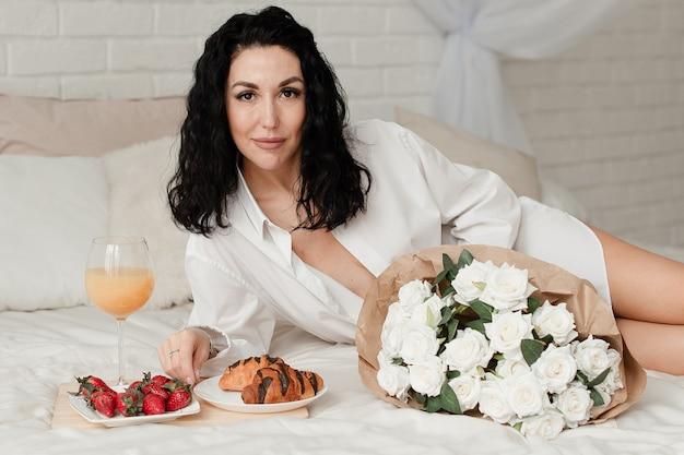 白いシャツのセクシーなブルネットモデルは、食べ物と一緒にベッドに横たわっています