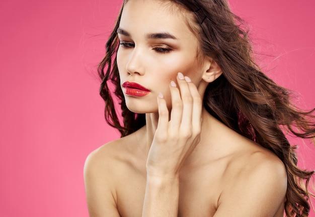 セクシーなブルネットモデルピンクの背景赤い唇のむき出しの肩