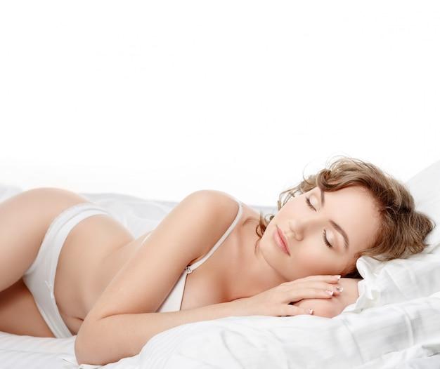 하얀 침대 시트에 섹시 한 갈색 머리입니다.