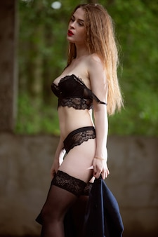 A sexy brunette with a beautiful body in black underwear and stockings