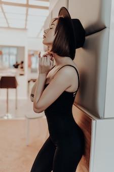 Donna sexy del brunette in vestito e cappello neri che si levano in piedi vicino alla parete in appartamento di lusso