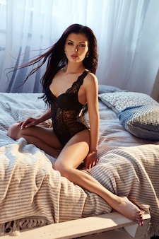 Sexy brunette woman in black lingerie at home on the bed.