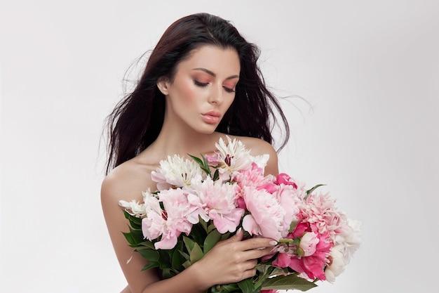 牡丹の花の大きな花束を保持しているセクシーなブルネットの女性