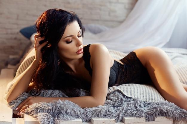 自宅のベッドで黒のランジェリーでセクシーなブルネットの女性。完璧な体型、美少女に美ボディ。なめらかで清潔な肌と強くしなやかな長い髪