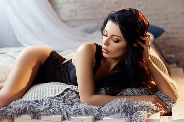 自宅のベッドで黒のランジェリーでセクシーなブルネットの女性。完璧な姿、女の子の美しい体。滑らかできれいな肌と長く強い髪。黄色いランプの光の中で少女