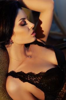 Сексуальная брюнетка женщина в нижнем белье дома, сидя на стуле. идеальная фигура, красивое тело на девушке. гладкая чистая кожа и длинные крепкие волосы. девушка в свете желтой лампы