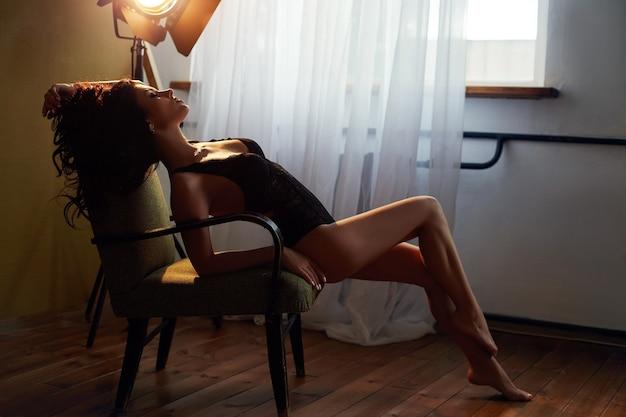 椅子に座って自宅でランジェリーのセクシーなブルネットの女性。完璧な姿、女の子の美しい体。なめらかで清潔な肌と長くて強い髪