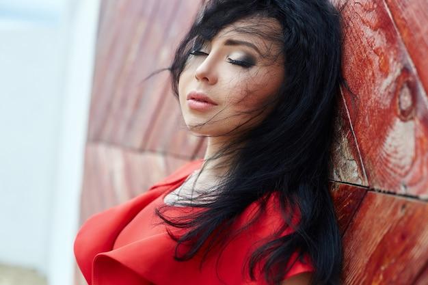 赤いドレスを着たセクシーなブルネットの女性が赤い門の近くに立っています。風になびく髪、ロマンチック、繊細な表情、セクシーな表情、美しい目