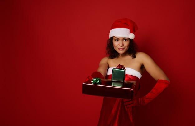 산타 카니발 복장을 한 섹시한 브루네트 여성은 한 손으로 허리를 잡고 선물 상자를 복사 공간이 있는 빨간색 배경 위에 뻗은 다른 손으로 포즈를 취합니다. 기쁜 성 탄과 새 해 복 많이 받으세요 개념