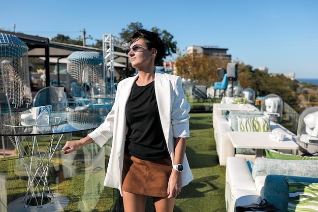 白いジャケット、黒いシャツ、レストランの革の茶色のスカートのセクシーなブルネットの女性。