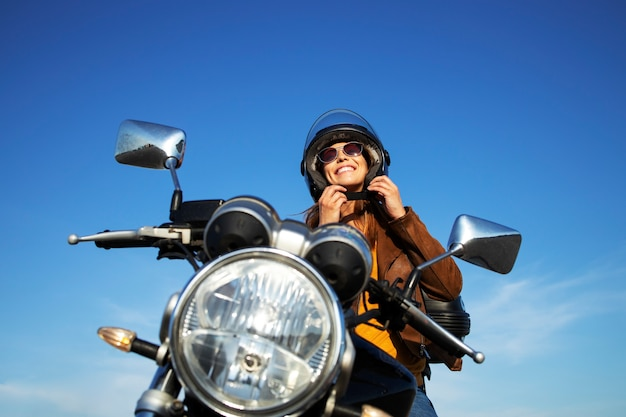 Sexy brunette woman in leather jacket putting helmet on and sitting on retro style motorcycle on beautiful sunny day