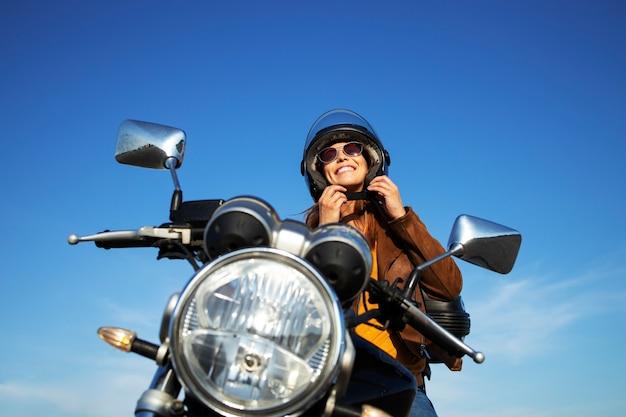 Donna castana sexy in giacca di pelle che mette il casco e che si siede sulla moto in stile retrò in una bella giornata di sole