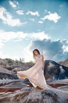 Sexy brunette woman in long dress standing in wind