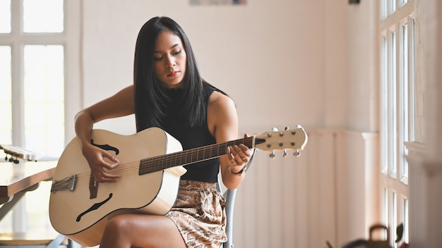 Sexy brunette woman playing an acoustic guitar while sitting at the modern chair