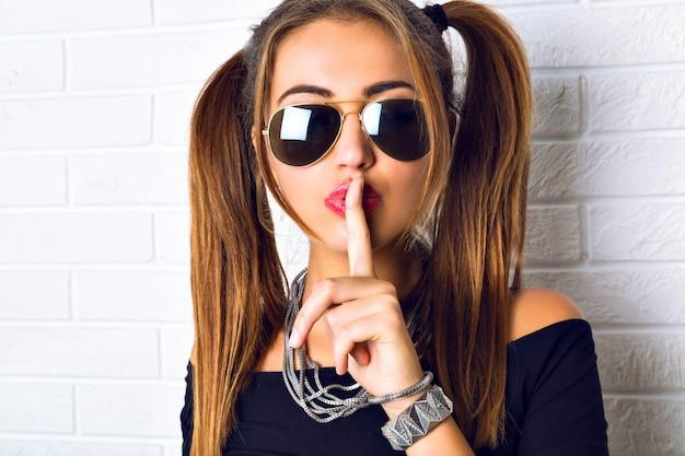 セクシーなブルネットの女性が都市のレンガの壁でポーズします。ファッションポートレートを閉じて、指を唇に当てて、シーッと言う