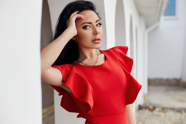 Sexy brunette woman in red dress stands near the walls of the old villas by the sea. portrait of a girl closeup, romantic sexual way. hair twisted in the wind. summer, holiday, travel