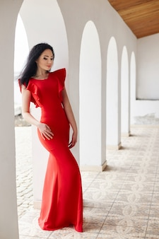 Sexy brunette woman in red dress stands near the walls of the old villas by the sea