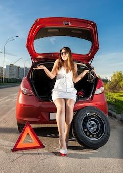壊れた車のトランクに座っているセクシーなブルネットの女性