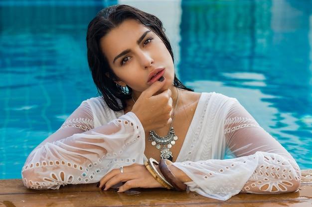 スタイリッシュな夏服でプールの近くに座っているセクシーなブルネットの女性。熱帯の休暇。