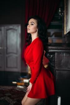 壁に寄りかかって赤い魅惑的な身に着けているセクシーなブルネットの女性。
