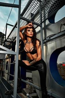 큰 도시를 배경으로 옥상에서 포즈를 취하는 아름다운 모습을 한 섹시한 갈색 머리 여자.