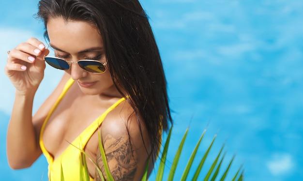 Donna brunetta sexy con abbronzatura dorata e tatuaggio, bikini con occhiali da sole, rilassante a bordo piscina.