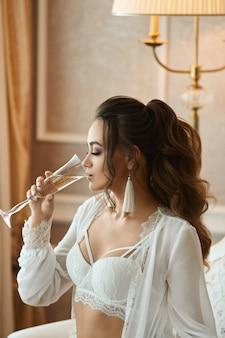 Сексуальная брюнетка с идеальным телом и свадебной прической в модном кружевном бюстгальтере и в ...