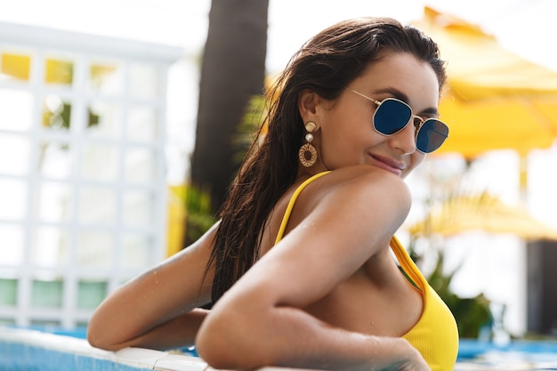 Sexy brunette woman in yellow bikini and sunglasses, relaxing in swimming pool, smiling and turn at camera.