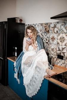 흰색 란제리에 포즈 섹시 한 갈색 머리 젊은 여자, 카메라를 봐. 손에 강한 커피 한잔. 긴 곱슬 머리. 섹시 한 여자 초상화입니다. 식탁에 앉아