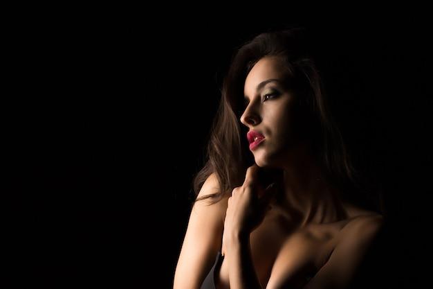 影の中で裸の肩でポーズをとって明るいメイクでセクシーなブルネットの若い女性